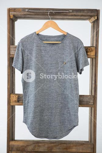 Grey t-shirt hanging on wooden frame