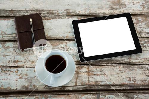 Digital tablet with cup of coffee and organiser