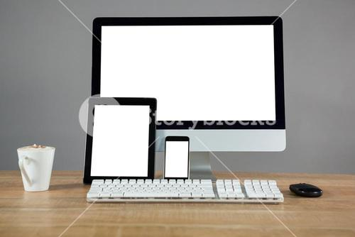 Coffee, desktop pc, digital tablet and smartphone on table
