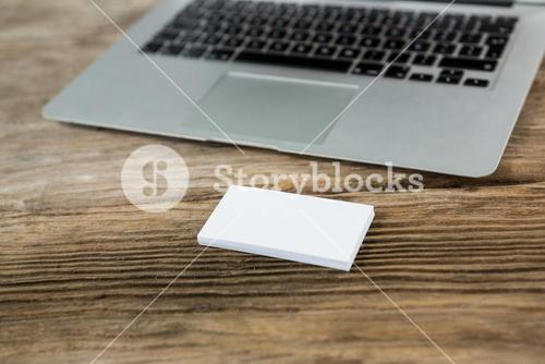 Laptop with sticky notes on wooden table