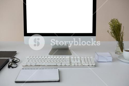 Desktop pc with coffee and diary on table