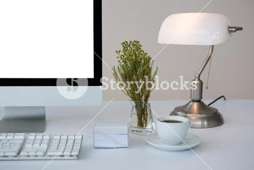 Desktop pc with coffee and table lamp on table