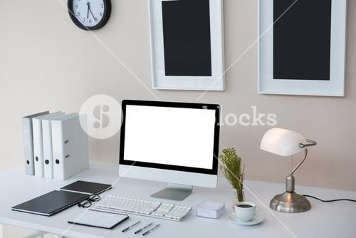 Desktop pc on desk with picture frames on wall