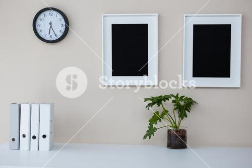 Picture frames and clock on wall