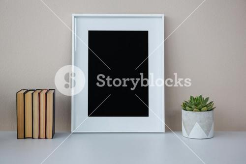 Books, picture frame and pot plant