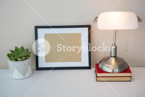 Picture frame, books, table lamp and potted plant on table