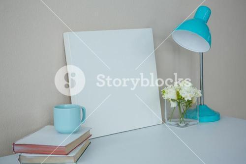 Picture frame, coffee cup with table lamp and flower vase