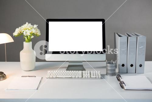 Desktop pc with flower vase and files