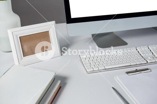 Picture frame, desktop pc and books on table