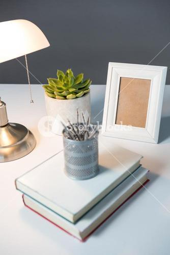 Table lamp, picture frame and books on table