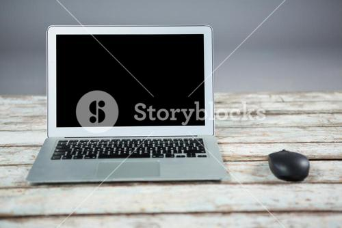 Laptop and mouse on wooden table