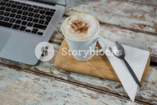 Cup of coffee and spoon with laptop