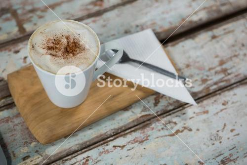 Cup of coffee and spoon on wooden tray