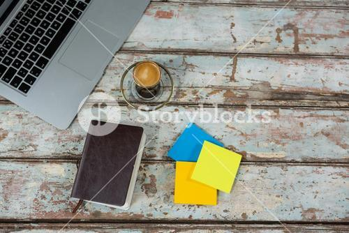 Laptop, sticky notes, and diary with cup of coffee