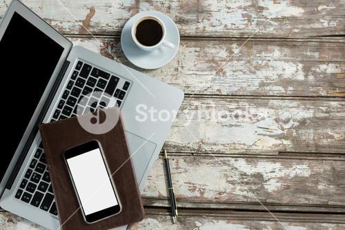Laptop, smartphone and diary with coffee cup