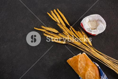 Baguette wrapped in napkin, wheat grains and flour