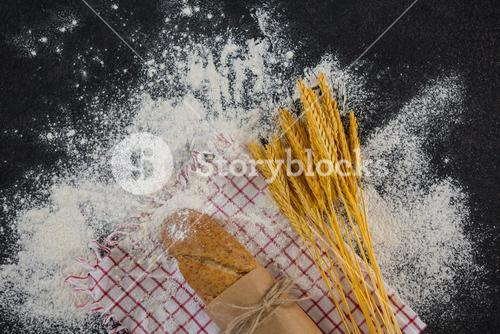 Baguette wrapped in paper, wheat grains and flour