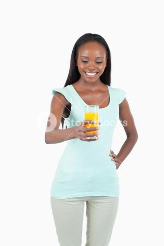 Smiling young woman holding a glass of orange juice