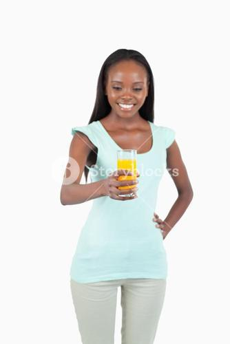 Glass of orange juice being held by smiling young woman