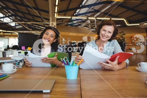 Smiling business executives holding document