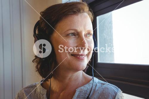 Smiling business executive listening to music on headphones