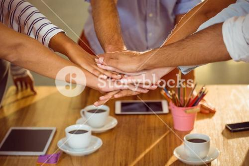 Mid section of business executives putting hands together