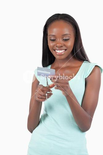 Happy smiling young female destroying credit card
