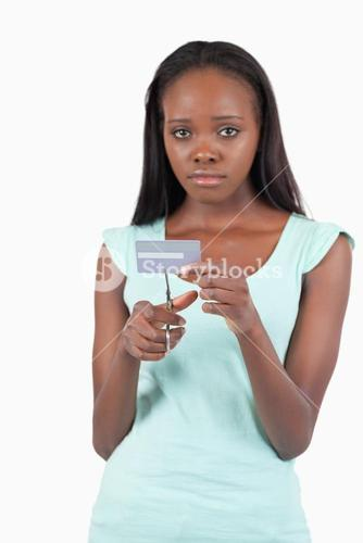 Sad woman cutting her credit card into pieces