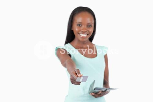 Smiling young woman using her credit card to pay