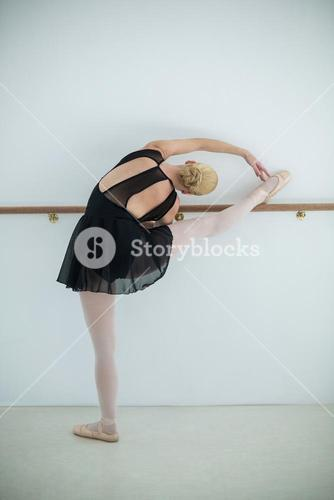 Ballerina stretching on a barre while practicing ballet dance