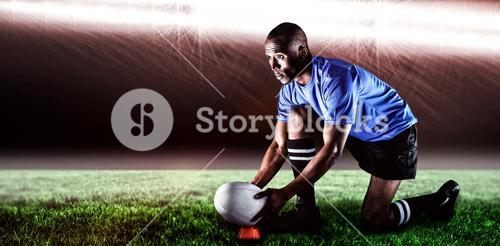 Composite image of rugby player looking away while keeping ball on kicking tee and 3d