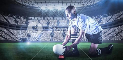 Composite image of rugby player looking away while keeping ball on kicking tee with 3d