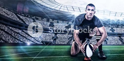 Composite image of portrait of rugby player in black jersey placing ball with 3d