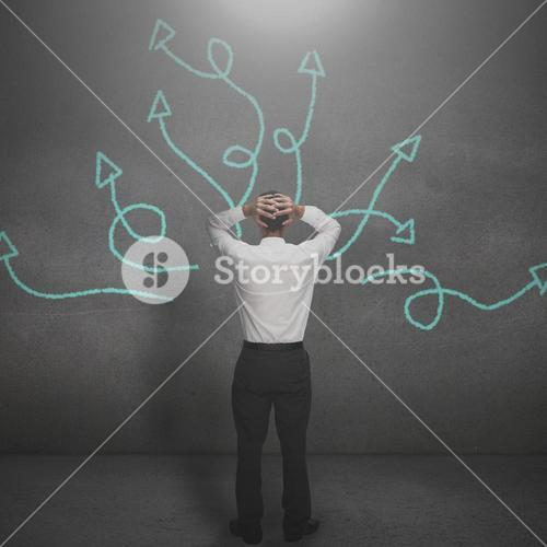 Stressed businessman looking at arrows