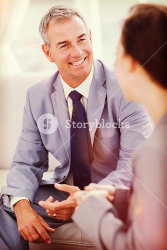 Smiling businessman talking to his workmate