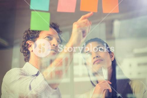 Business people reading adhesive notes