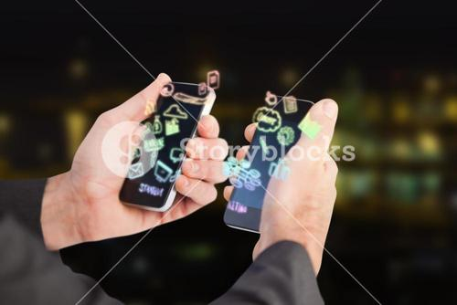 Composite image of businessman holding a phone in each hand 3d