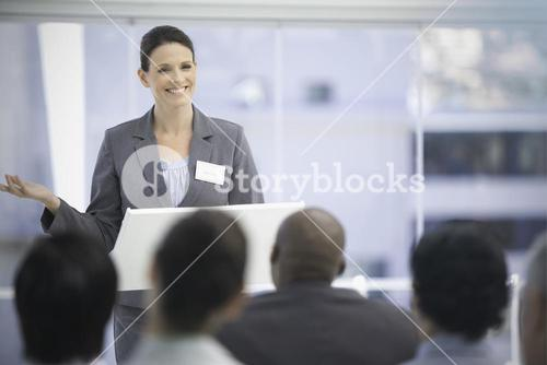 Smiling businesswoman gesturing while her colleagues watch her