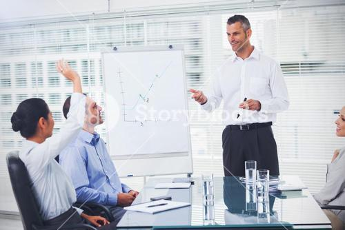 Businesswoman asking question during her colleagues presentation