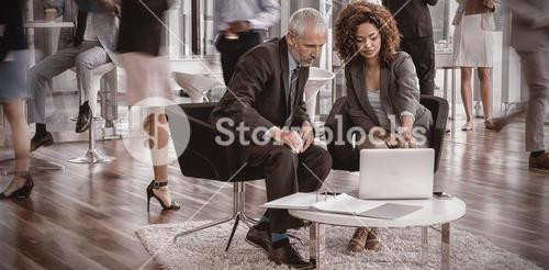 Business people looking into laptop