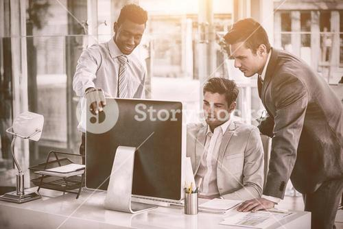 Focused business people looking into computer