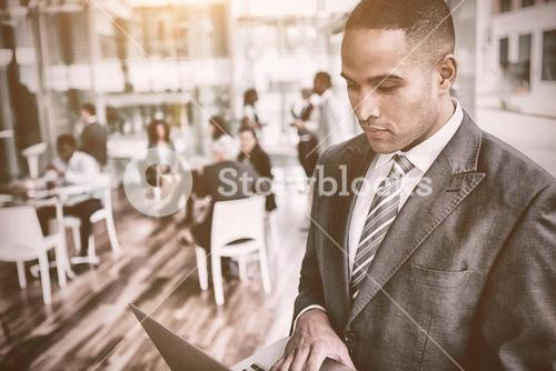 Concentrated businessman using laptop