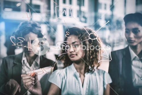 Businesswoman writing with marker on glass