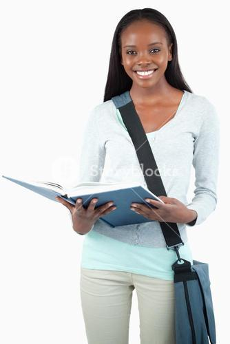Smiling young student with bag reading in her book