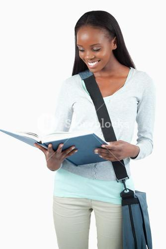 Smiling student with bag reading in her book