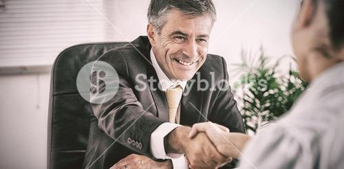 Man shaking a womans hand in an office