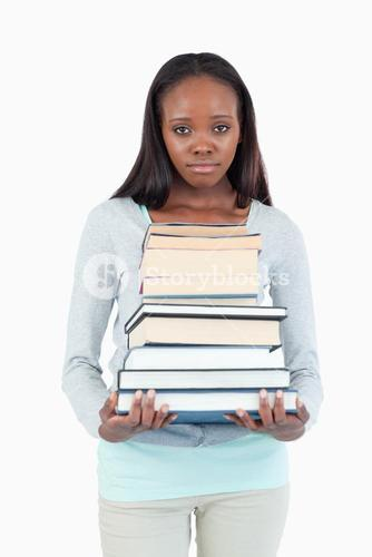 Sad looking young woman with stack of books