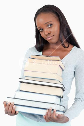 Sad smiling woman with pile of books