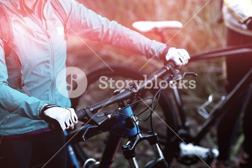 Midsection of female biker with mountain bike