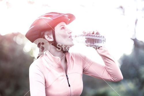 Female cyclist drinking water in forest